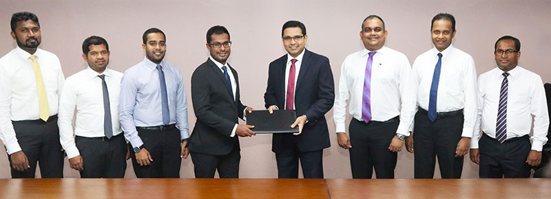 Commercial Bank's Chief Operating Officer Mr Sanath Manatunge (4th from right) and Chief Executive Officer of JAT Holdings Mr Nishal Ferdinando exchange the agreement in the presence of Commercial Bank Deputy General Manager – Marketing Mr Hasrath Munasinghe (3rd from right) and senior representatives of the two institutions.