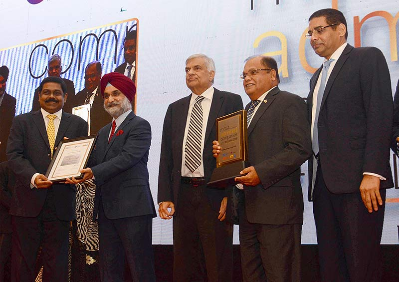 Commercial Bank Chairman Mr Dharma Dheerasinghe (second from right) and Managing Director Mr S. Renganathan (extreme left) with the award presented by the Prime Minister Hon. Ranil Wickramasinghe.