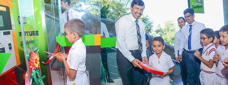 A student opening the school banking unit, consisting of a cash deposit machine, while K. B. Rajapaksa - Senior DGM – Retail Banking hands over a gift