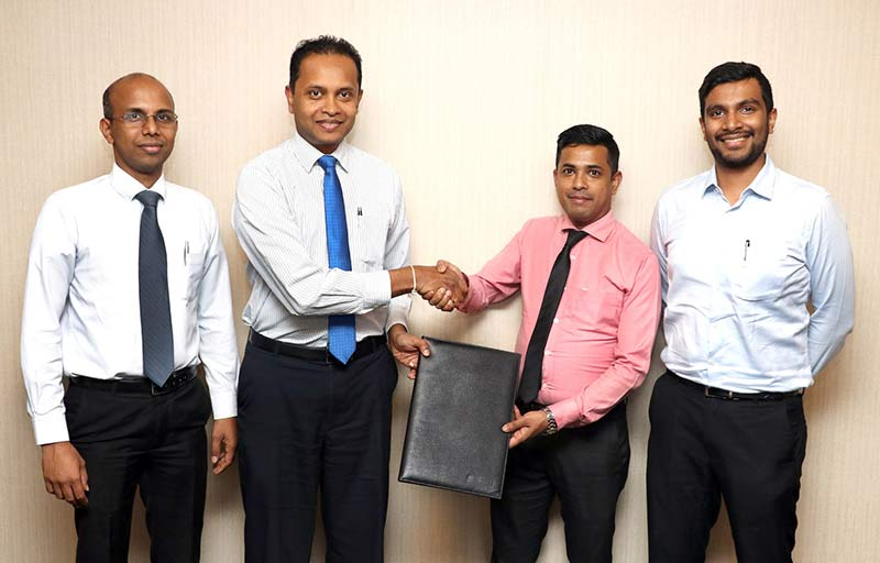 Commercial Bank's Head of Card Centre Mr Thusitha Suraweera (2nd from left) and Fashion Bug Area Manager Mr Mohamed Faishad exchange the agreement in the presence of Fashion Bug CEO Mr Aqeill Ahamed Subian (extreme right) and Junior Executive Officer of the Bank's Card Centre Mr Wishan Fernando.