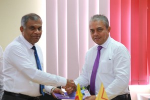 Post Master General Ranjith Ariyaratne (left) and Softlogic Life Managing Director Iftikar Ahamed exchanging the agreement