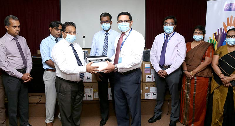 Commercial Bank's Chief Operating Officer Mr Sanath Manatunge (4th from right) presents the equipment to the Director of the National Hospital Kandy Dr Saman Rathnayake in the presence of representatives of the senior and corporate management of the Bank and staff of the hospital.