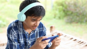 Indian Cute boy listening to music and using mobile phone